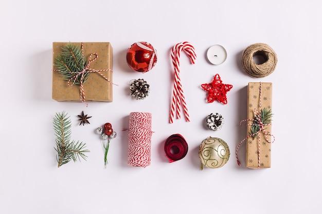 Kerstdecoratie samenstelling geschenkdoos dennenappels bal vuren takken kaars Gratis Foto