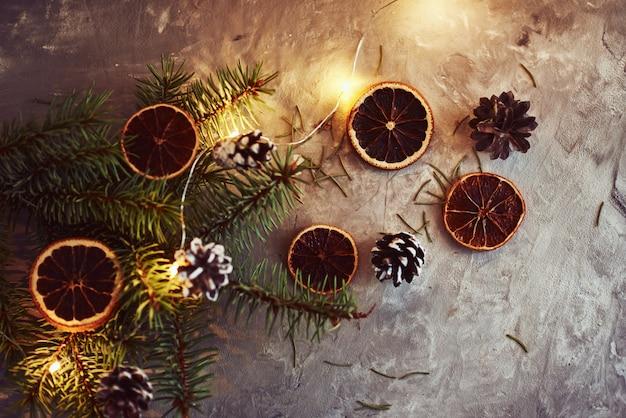 Kerstdecoraties met slingerlichten, dennenappels en sparrentak Premium Foto