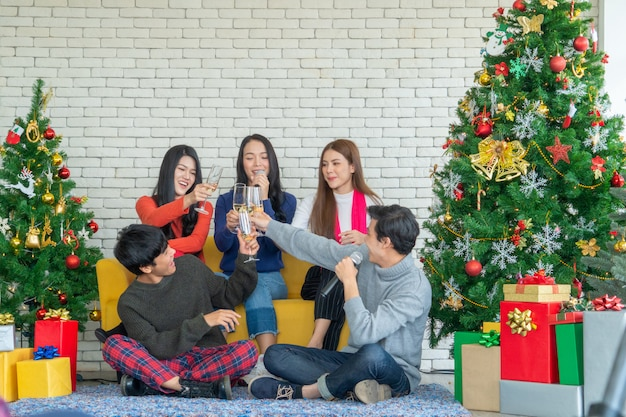 Kerstfeest tijd. jonge aziatische mensen die met champagnefluiten roosteren. vrienden feliciteren elkaar met nieuwjaar. Premium Foto