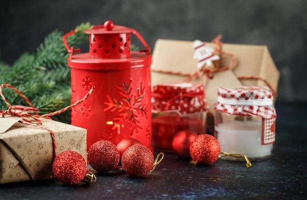 Kerstgeschenkdoos, rode lantaarn met kaars, rode ballen en decoratielicht Premium Foto