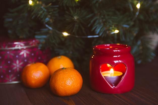 Kerstkaars, boom, mandarijnen. Premium Foto