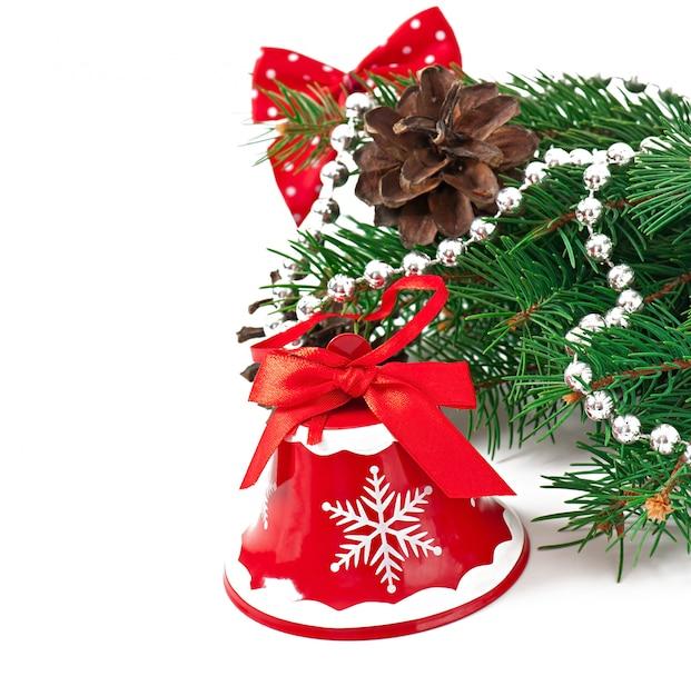 Kerstkaart met een rode bel en dennentakken Gratis Foto
