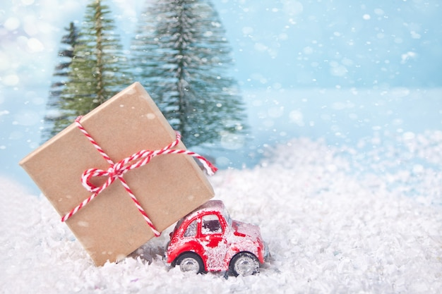 Kerstkaart voor kerstmis en nieuwjaar. vakantie samenstelling met pijnbomen, rode speelgoedauto en geschenkdoos. Premium Foto