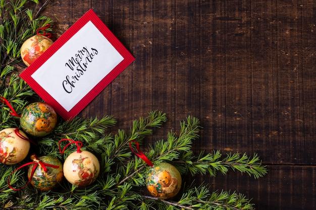 Kerstkaartmodel met ornamenten op houten achtergrond Gratis Foto