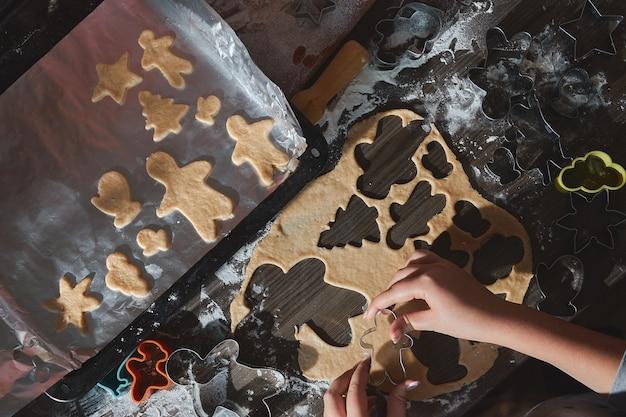 Kerstkoekjes bakken op donkere bruine houten tafel. familie die peperkoekman maken, koekjes van peperkoekdeeg, van bovenaf bekijken. Premium Foto