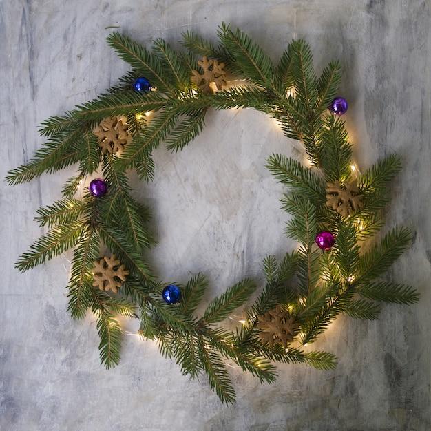 Kerstkrans gemaakt van dennentakken, koekjes, gekleurde ballen en gloeiende lichten. Premium Foto