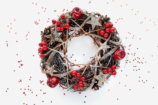 Kerstkrans gemaakt van takken versierd met gouden houten sterren en bubbels van rode bessen op witte achtergrond. creatieve doe-het-zelfhobby. Premium Foto