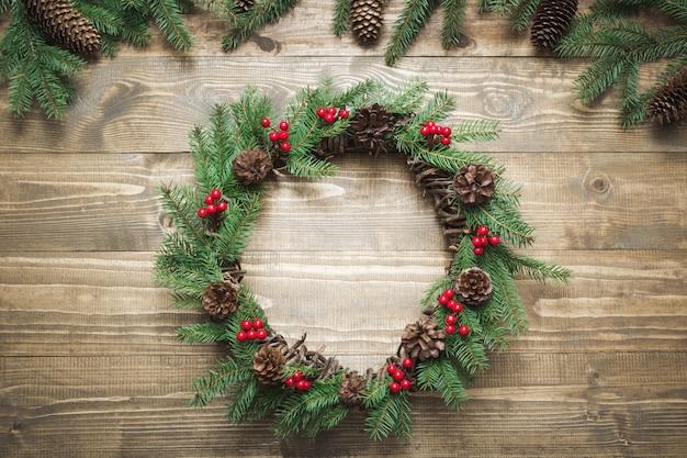 Kerstkrans gemaakt van vuren takken met hulst bessen op houten bord. Premium Foto