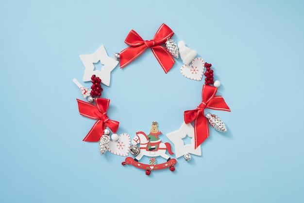 Kerstkrans met rode en witte decoraties op pastel blauwe achtergrond. nieuwjaar concept. Premium Foto