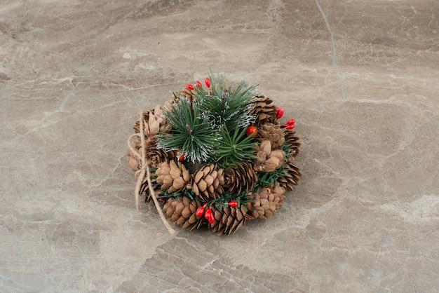 Kerstkrans met rode kralen en kegels op marmer. Gratis Foto