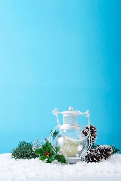 Kerstlantaarn op sneeuw met spartak en winterdecoratie op blauw. vakantie kerst concept. Premium Foto
