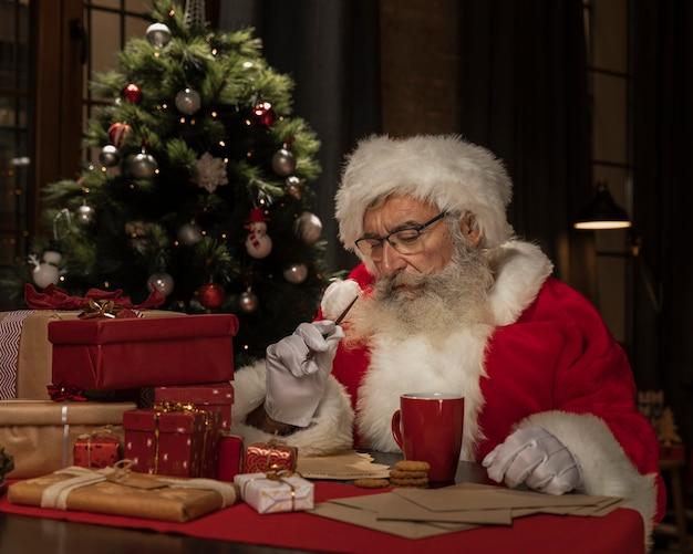 Kerstman aan tafel denken Gratis Foto