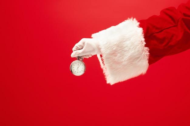 Kerstman die een chronometer op rode achtergrond houden. seizoen, winter, vakantie, feest, cadeau-concept Gratis Foto