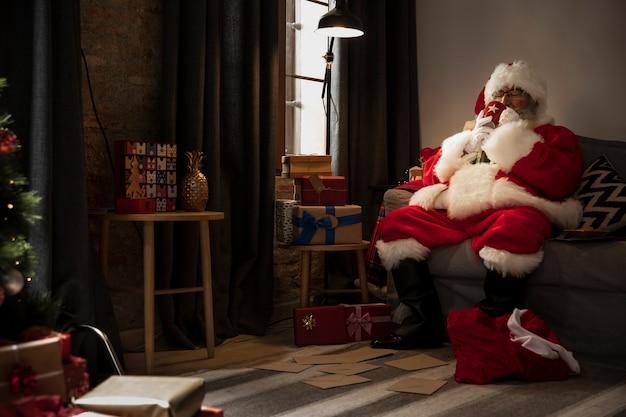 Kerstman die een kopje koffie drinkt Gratis Foto