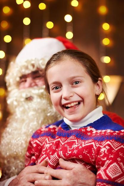 Kerstman en kind meisje poseren samen binnen in de buurt van ingericht Premium Foto