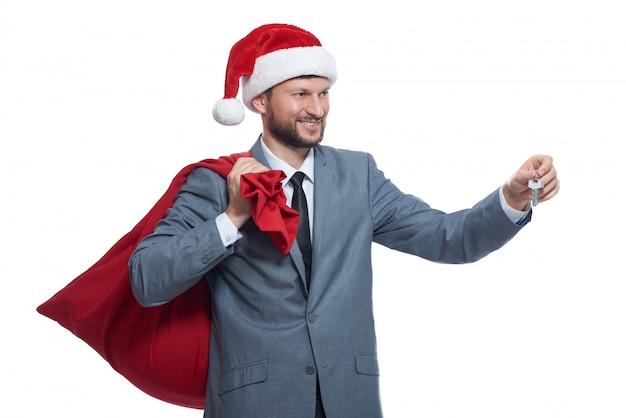 Kerstman in grijze suite, rode pet met volle tas over de schouder, glimlachend, wegkijken, sleutel geven. Gratis Foto