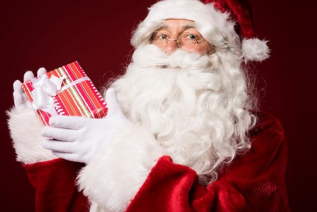 Kerstman met een geschenkdoos op rode achtergrond Gratis Foto
