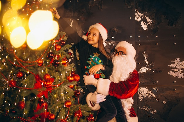 Kerstman met meisje kerstboom versieren samen Gratis Foto