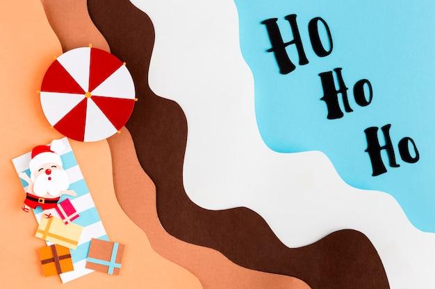 Kerstman op het strand bovenaanzicht papierstijl Premium Foto