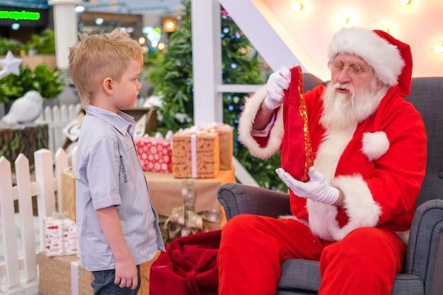 Kerstman praten en verrassingsspellen spelen met kinderen in winkelcentrum Premium Foto