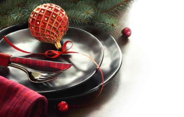 Kerstmenu concept met versierde zwarte borden en bestek Premium Foto