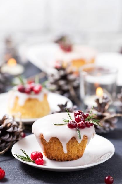 Kerstmis cupcake met suikersuikerglazuur, amerikaanse veenbessen en rozemarijn Premium Foto