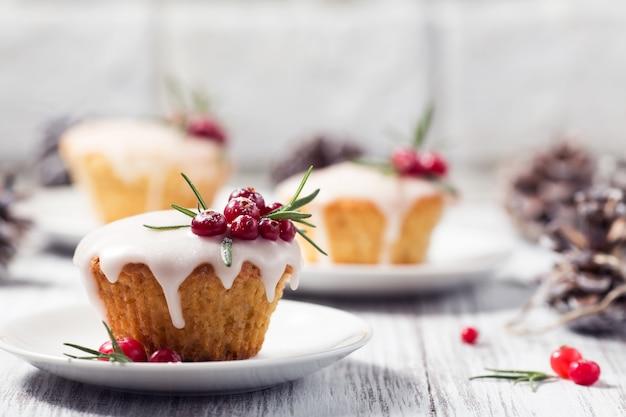 Kerstmis cupcakes met suikersuikerglazuur, amerikaanse veenbessen en rozemarijn Premium Foto