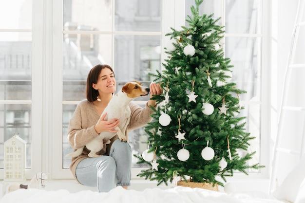 Kerstmis en feest. de gelukkige huisvrouw met brede glimlach, stelt dichtbij verfraaide spar met hond die snuisterij ruikt Premium Foto