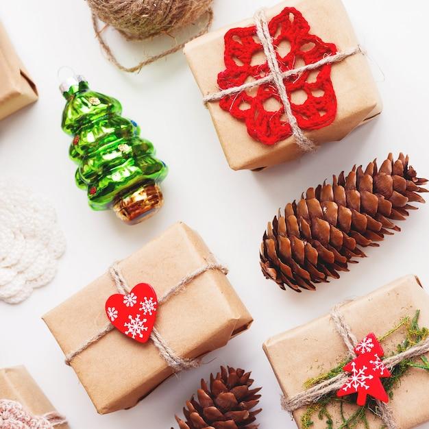 Kerstmis en nieuwjaar achtergrond met handgemaakte cadeautjes verpakt in kraft papier en decoraties. Premium Foto