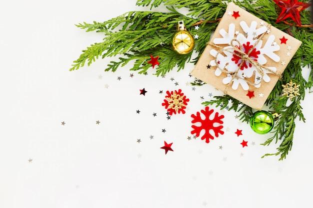 Kerstmis en nieuwjaar achtergrond met thuja tak, decoraties en heden verpakt in kraft papier met sneeuwvlokken. Premium Foto