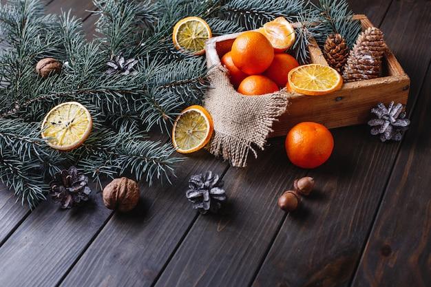 Kerstmis en nieuwjaar decor. sinaasappelen, kegels en takken van de kerstboom Gratis Foto