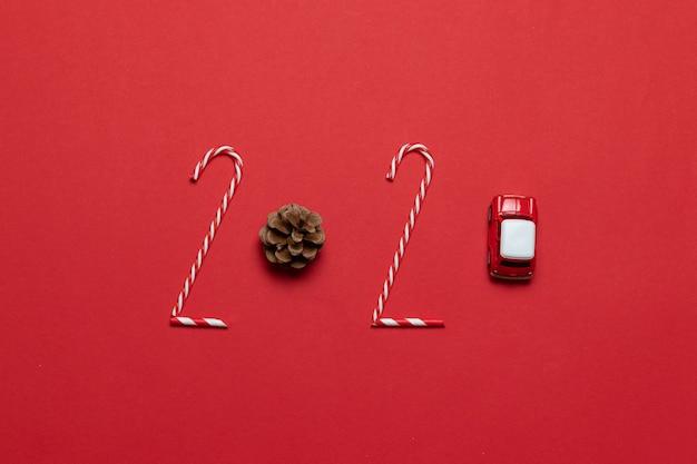 Kerstmis en nieuwjaar vakantie 2020 inscriptie van verschillende versierde objecten klassieke rode glazen kerstballen bal, speelgoedauto op een rode achtergrond. horizontale rand. Premium Foto