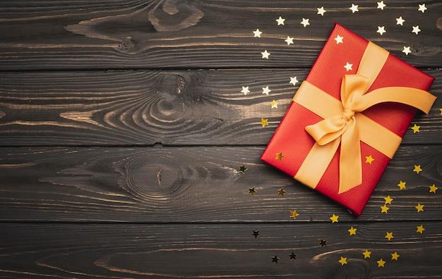 Kerstmis huidig op houten achtergrond en gouden sterren Gratis Foto