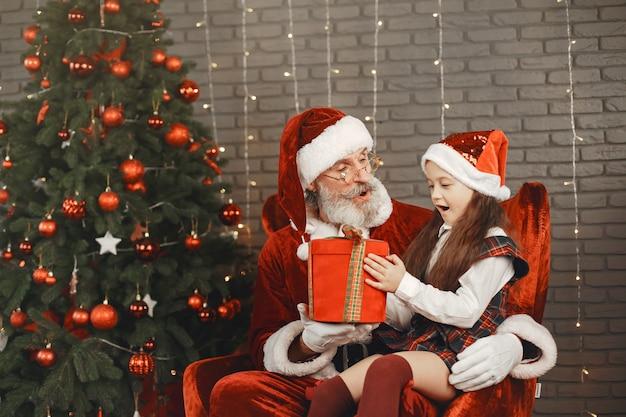 Kerstmis, kind en geschenken. de kerstman bracht cadeautjes voor het kind. blij meisje dat kerstman koestert. Gratis Foto