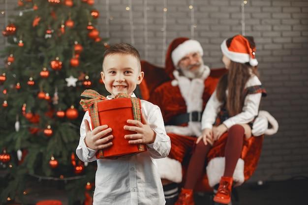 Kerstmis, kinderen en cadeaus. de kerstman bracht cadeautjes voor kinderen. vrolijke kinderen met geschenken die santa knuffelen. Gratis Foto