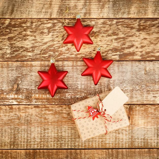 Kerstmis met rode decoratiesterren en ballen en giftdozen op houten raad Premium Foto