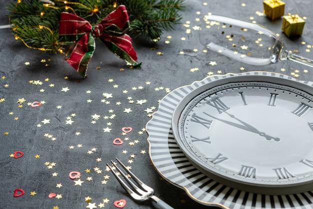 Kerstmis, nieuwjaarsviering - klokvormige schotel, champagneflessen, twee champagneglazen en gouden glitter confetti, Premium Foto