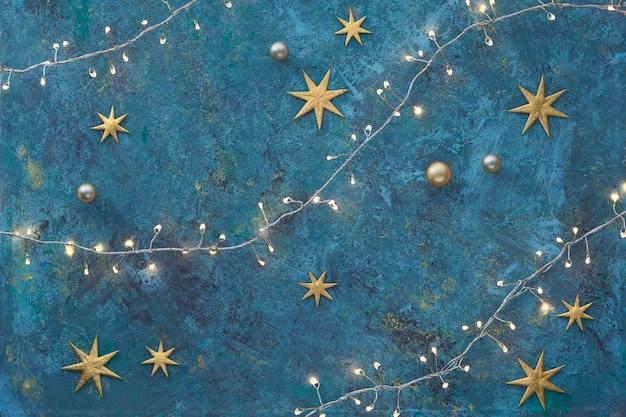 Kerstmis of nieuwjaar plat lag achtergrond op donkere grunge getextureerde bord. bovenaanzicht, plat lag met lichten op xmas lichtslinger, gouden kerstballen en glanzende sterren. vrolijk kerstfeest en een gelukkig nieuw jaar! Premium Foto