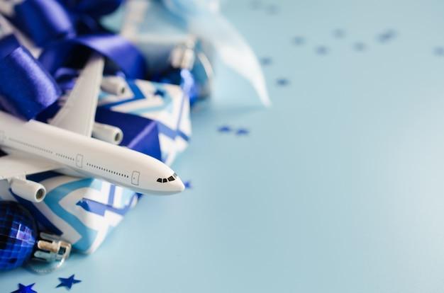 Kerstmis of nieuwjaar reizen concept. stuk speelgoed vliegtuig met paspoorten en giftdozen op blauwe achtergrond. Premium Foto