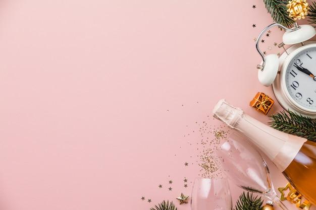 Kerstmis of nieuwjaarsamenstelling op roze achtergrond met retro wekker, fles champagne, glazen en kerstmisdecoratie Premium Foto