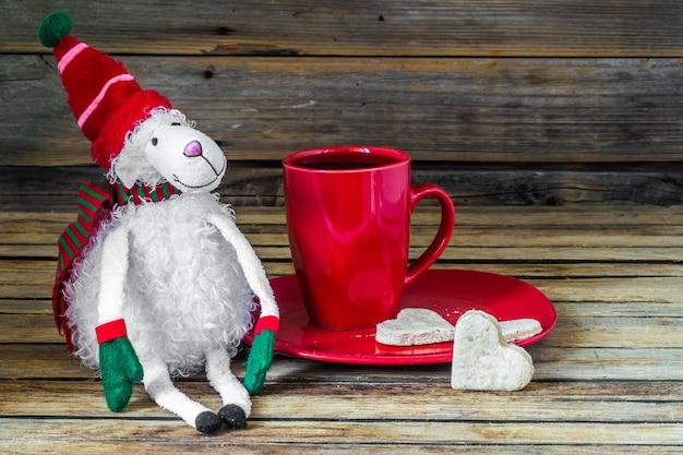 Kerstmis, rode kop met koffie en dessert op houten tafel Gratis Foto