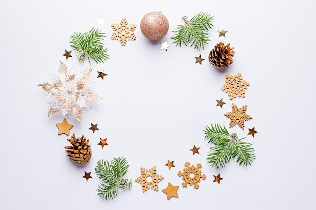 Kerstmis rond frame met dennentakken, dennenappels, confetti op grijs, kopie ruimte. Premium Foto