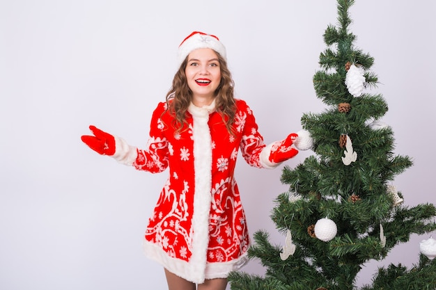 Kerstmis, vakantie en emotiesconcept - verraste kerstmanvrouw dichtbij kerstboom op witte muur. Premium Foto
