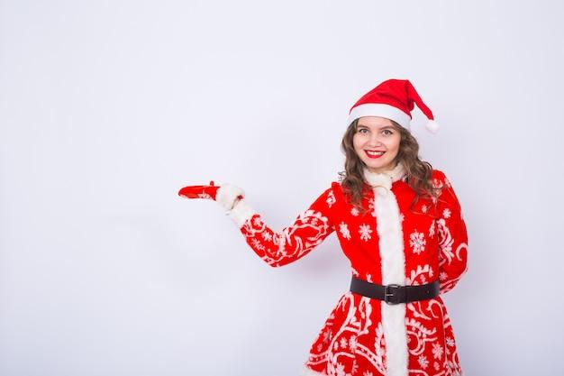 Kerstmis, vakantie en mensenconcept - de vrouw is santakostuum dat naar witte muur met exemplaarruimte richt. Premium Foto