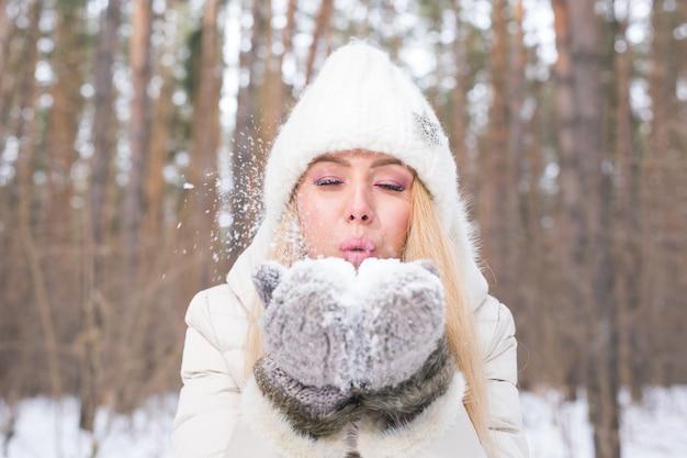 Kerstmis, vakantie en seizoenconcept - jonge gelukkige blonde vrouwen blazende sneeuw in de winteraard Premium Foto