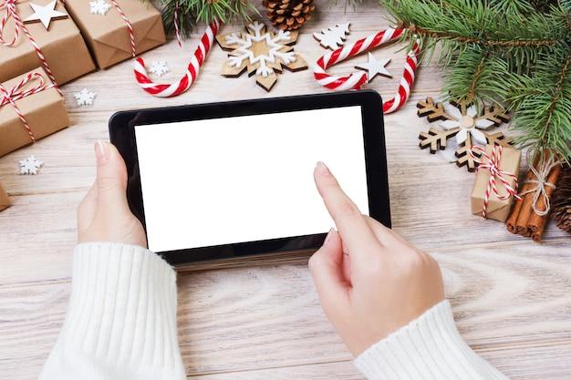 Kerstmis van vrouwelijke handen gebruikt geopende tablet op rustieke houten die lijst met kerstmisdecoratie wordt behandeld, hoogste vlakke mening, legt Premium Foto