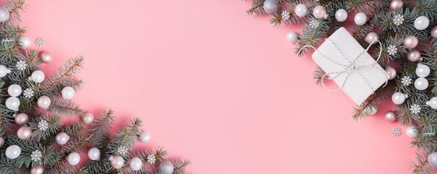 Kerstmis zilveren roze glazen bol en dennentakken op roze Premium Foto