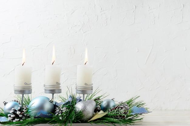 Kerstmisachtergrond met blauwe ornamenten en brandende kaarsen Premium Foto