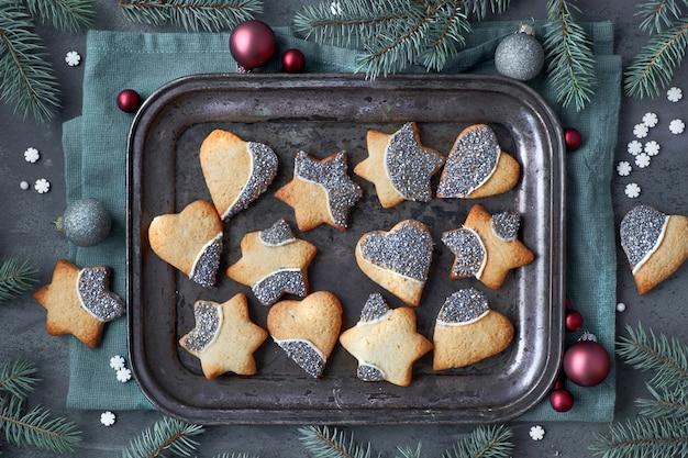 Kerstmisachtergrond met kerstmiskoekjes in vorm van harten en sterren op metaaldienblad Premium Foto