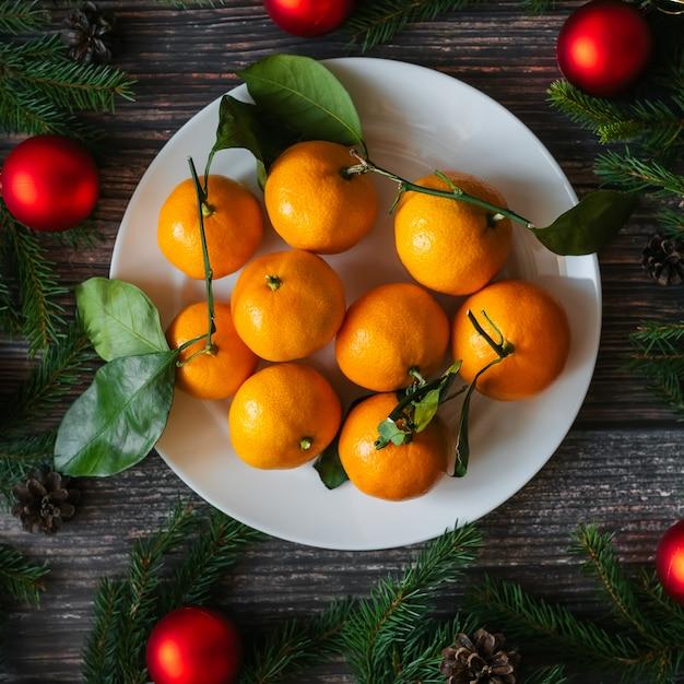 Kerstmisachtergrond met mandarins, spartakken, rode ballen en denneappels op houten lijst Premium Foto